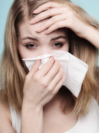 Flu cold or allergy symptom. Sick woman girl with fever sneezing in tissue on blue. Health care. photo