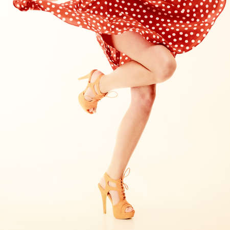piernas sexys: Estilo Vintage modelo. Piernas femeninas atractivas en la danza en rosa. Chica en el retro vestido manchado de rojo y naranja bailando tacones altos. Parte.