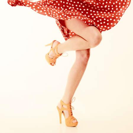 sexy beine: Pinup-Stil. Sexy Frauen Beine in Tanz auf Rosa. Mädchen in der Retro gesichtet roten Kleid und orange High Heels zu tanzen. Partei.