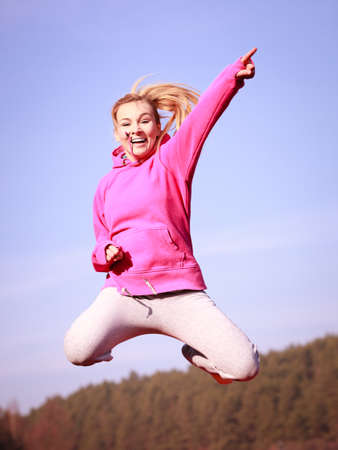 sweatsuit: Full length of cheerful woman teenage girl in pink tracksuit jumping high showing pointing at something outdoor. Healthy active lifestyle.