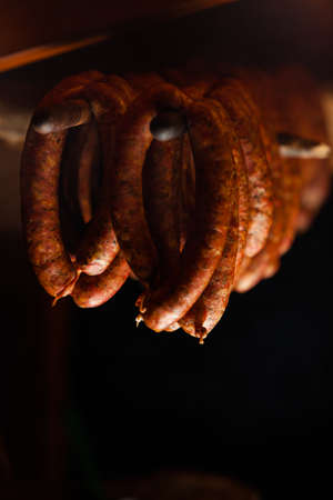 Traditional food. Smoked sausages meat hanging in domestic smokehouse. photo