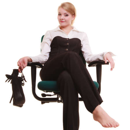 Break from work. Young businesswoman happy girl with shoes in hand relaxing on chair isolated on white. Copy space. Business. photo