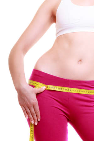Time for diet slimming weight loss. Health care and healthy nutrition. Young fitness woman fit girl with measure tape measuring her loins isolated on white photo