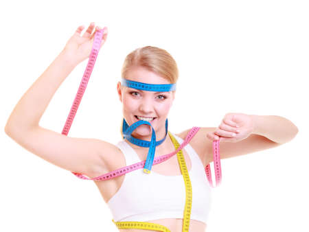 obsessed: Time for diet slimming weight loss. Health care healthy lifestyle. Fit fitness woman with a lot of colorful measure tapes. Obsessed girl by her body. Stock Photo