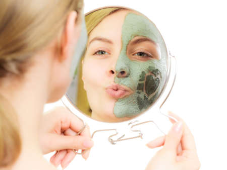 Skin care. Woman in clay mud mask on face with heart on cheek. Girl looking in the mirror and blowing a kiss isolated on white. Beauty treatment. photo