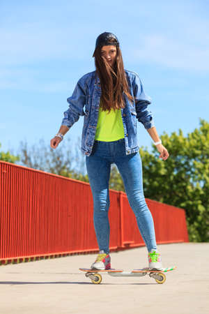 Summer sport and active lifestyle. Cool teenage girl skater\ riding skateboard on the street. Outdoor.