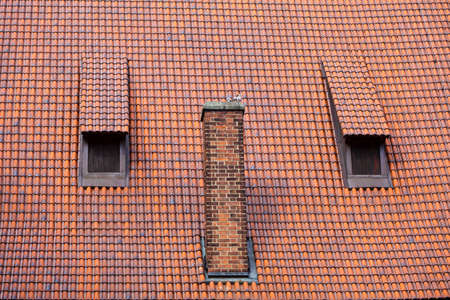 mansard: Architecture detail chimney red tile garret roof with windows old town Gdansk Poland Stock Photo