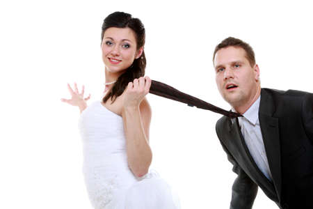Humorous funny wedding couple bride and groom - woman pulling the tie of a man, photo