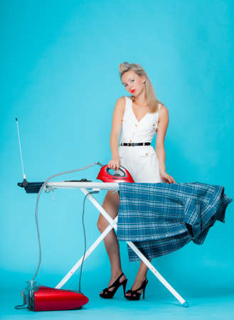 Full length girl retro style ironing male shirt, woman housewife in domestic role. Traditional sharing household chores.  Pin up housework.  Vivid blue background photo