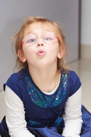 ittle: Portrait of cute ittle girl in red eyeglasses  Child making funny face  Kid doing fun indoor