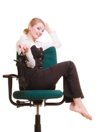 Break from work  Young businesswoman happy girl with shoes in hand relaxing on chair isolated on white  Copy space  Business  photo