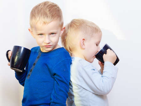 sibling rivalry: Happy childhood  Two brothers funny little boys children kids standing back to back drinking tea  Sibling rivalry