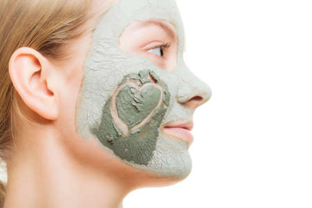 mud girl: Skin care  Woman in clay mud mask with heart symbol of love on cheek isolated on white  Girl taking care of dry complexion  Beauty treatment  Stock Photo