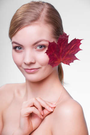capillary: Skincare habits  Portrait of young woman with leaf as symbol of red capillary skin on gray  Face of girl taking care of her dry complexion  Studio shot