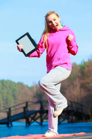 Full length of fitness woman sport teenage girl in pink tracksuit showing blank copy space screen of tablet touchpad computer outdoor  Electronic technology  Stock Photo