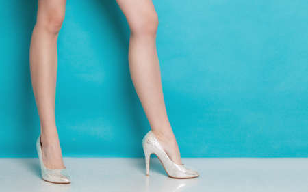 Female fashion. Closeup of silver high heels fashionable shoes on legs on blue. Studio shot. Zdjęcie Seryjne