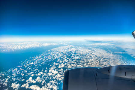 Blue sky and engine. View from window of airplane flying in clouds. Skyscape cloudscape. Birds eye. photo
