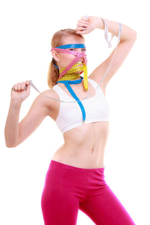 obsessed: Time for diet slimming weight loss. Health care healthy lifestyle. Fit fitness woman with a lot of colorful measure tapes around her head. Obsessed girl by body.
