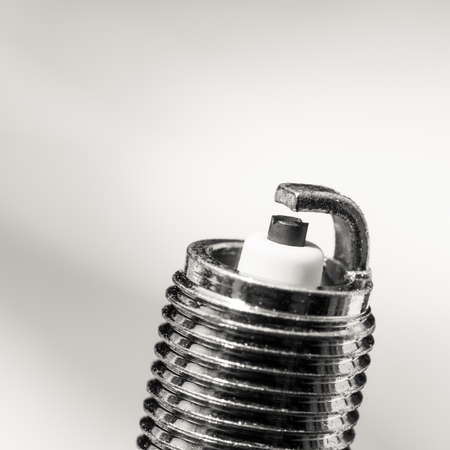Auto service. New car spark plug as spare part of auto transportation on gray background. photo