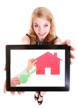 Real estate agent businesswoman showing pad with photo of paper house and keys. Happy blond girl holding tablet touchpad dreaming about own home. Isolated. Technology and accommodation. photo