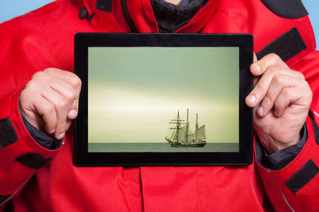 Closeup of male hands holding pad with photo of cruise ship. Man traveler showing screen tablet touchpad dreaming about adventure trip. Technology and travel. photo