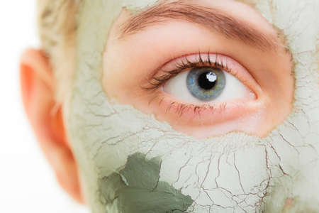 Woman in clay mud mask on face isolated on white. Girl taking care of dry complexion.