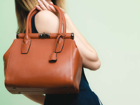 Closeup of brown leather bag handbag in hand of stylish woman fashionable girl on green.  Stock Photo