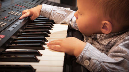 midi: Happy childhood and music. Little boy child kid playing on the black digital midi keyboard piano synthesizer musical instrument indoor.