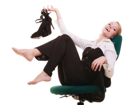 stoppage: Work stoppage  Happy smiling blonde businesswoman sitting on chair with shoes in hand  Business concept  Isolated on white  Studio shot   Stock Photo