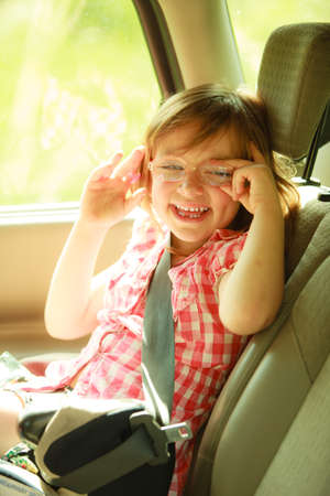 Road transportation  Little girl child kid in eyeglasses having fun in the back of car and going on a trip travel  photo