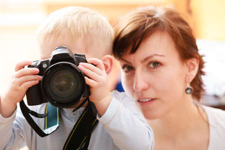 Happy childhood  Mother and her son boy child kid playing with camera taking photo  At home  Real  photo