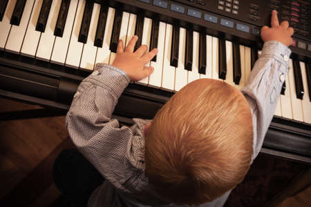Little boy child kid playing on the black digital midi keyboard piano synthesizer musical instrument indoor. photo