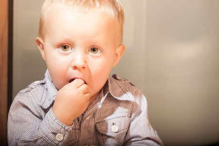 Happy childhood. Portrait of cute little boy child kid eating something at home. Healthy diet and nutrition. photo