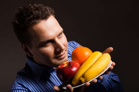 Happy young man smelling fruits on dark gray.  photo
