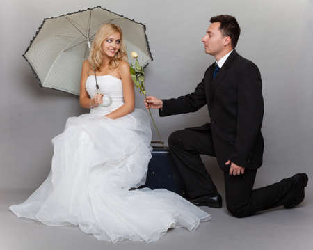 enamored: Wedding day. Portrait of romantic married couple blonde bride with umbrella and enamored groom giving a rose to girl. Full length studio shot gray background