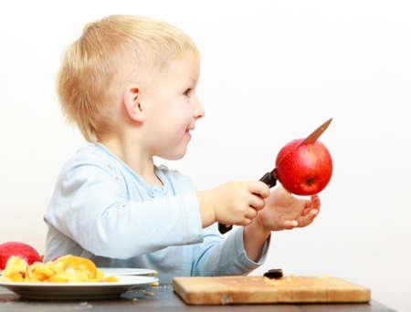 Blond boy child kid preschooler with kitchen knife cutting fruit apple at home.  photo