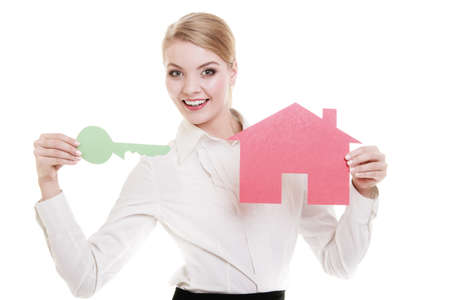 Woman real estate agent holding red paper house and key. Property business and accomodation or home buying ownership concept, isolated on white background Stock Photo
