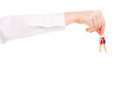 accommodation broker: Female hand real estate agent holding set of keys to new house or car. Property business and accomodation or home buying ownership concept, isolated on white background Stock Photo
