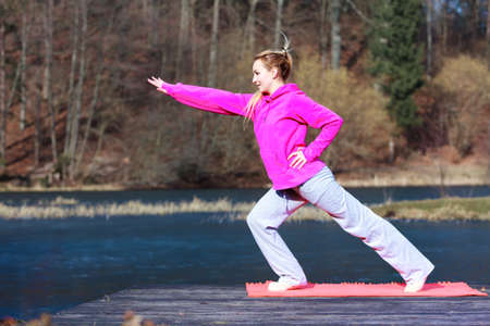 Full length of young woman teenage girl in pink tracksuit doing morning exercise on mat on pier outdoor. Healthy active lifestyle. photo