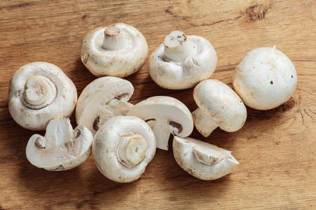 fungoid: Vegetarian food. Fresh white mushrooms champigonons on wooden kitchen table.
