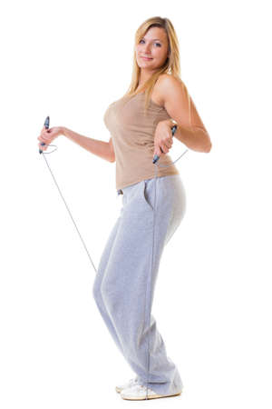 Sport girl plus size doing exercise with skip jump rope - weight loss. Fitness young woman isolated. Studio shot. photo