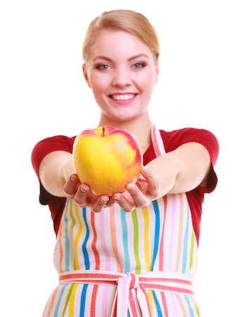 Happy housewife or chef in colorful kitchen showing red yellow apple healthy fruit isolated studio shot. Diet and nutrition. photo