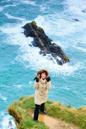 Irish atlantic coast. Woman tourist standing on rock cliff by the ocean Co. Cork Ireland Europe. Beautiful sea landscape natures beauty. photo