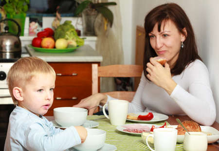 Family mother and blond son boy kid child eating corn flakes and bread breakfast morning meal at the table. Home. photo