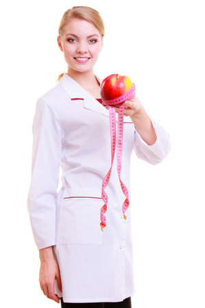 Woman in white lab coat recommending healthy food. Doctor dietitian holding fruit apple and measture tape isolated. Diet. photo