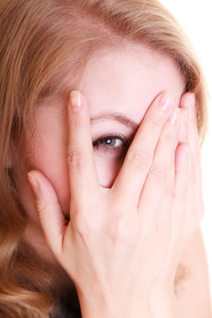 Portrait of afraid frightened woman peeking through her fingers isolated on white. Shy girl covering face with hands.