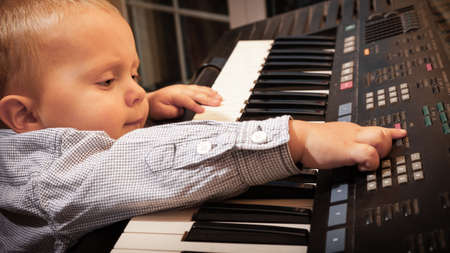 Happy childhood and music. Little boy child kid playing on the black digital midi keyboard piano synthesizer musical instrument indoor. photo