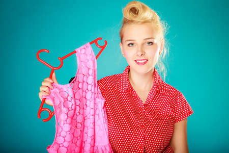 shopaholism: Pinup blond girl young woman in retro style buying clothes. Client customer holding pink dress on vibrant blue. Retail and sale. Studio shot.