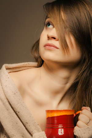 Hot beverage. Sleepy girl holding cup mug of drink tea or coffee. Woman in warm sweater warming herself photo