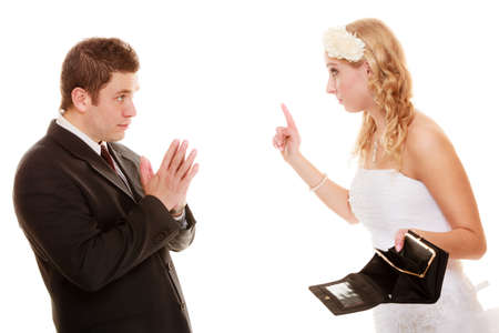 Marriage and money concept of high wedding cost. Angry bride with empty purse and groom quarrelling isolated on white. Bad relationship and conflict. Stock Photo